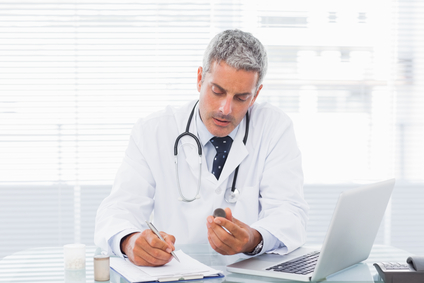 Doctor holding medication and writing a prescription at medical office